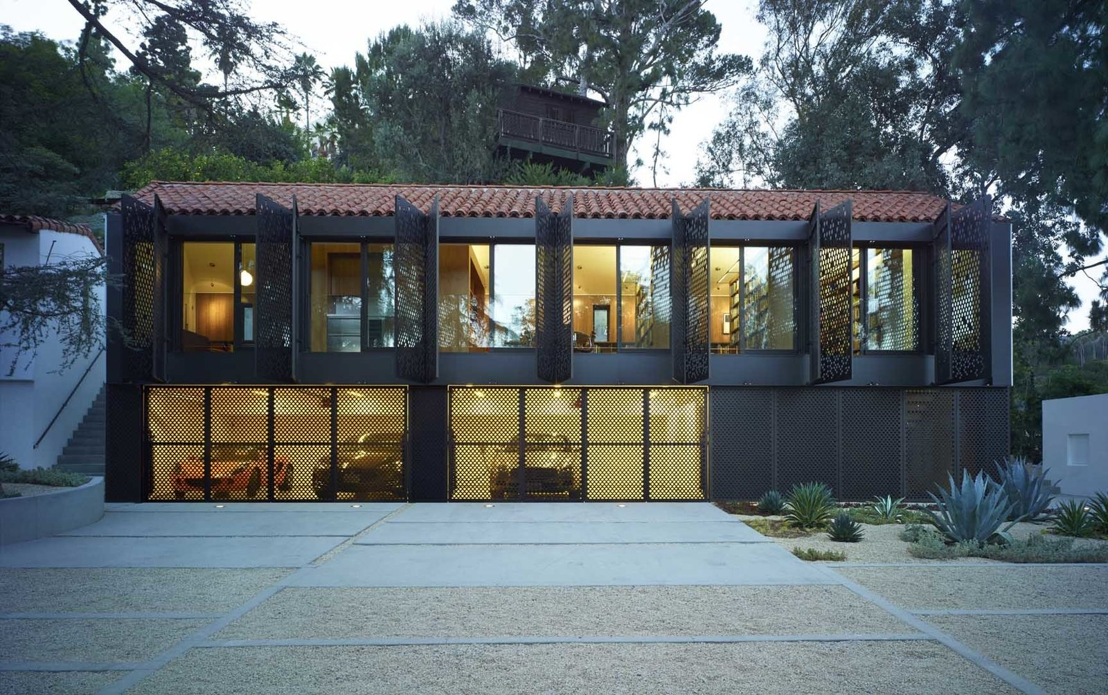 The building addition's most distinct feature is its metal screen façade.  The screens open like shutters for clear views of the property, and when shut, allows for privacy, sun shading and environmental control.  Morgan Phoa Library and Residence