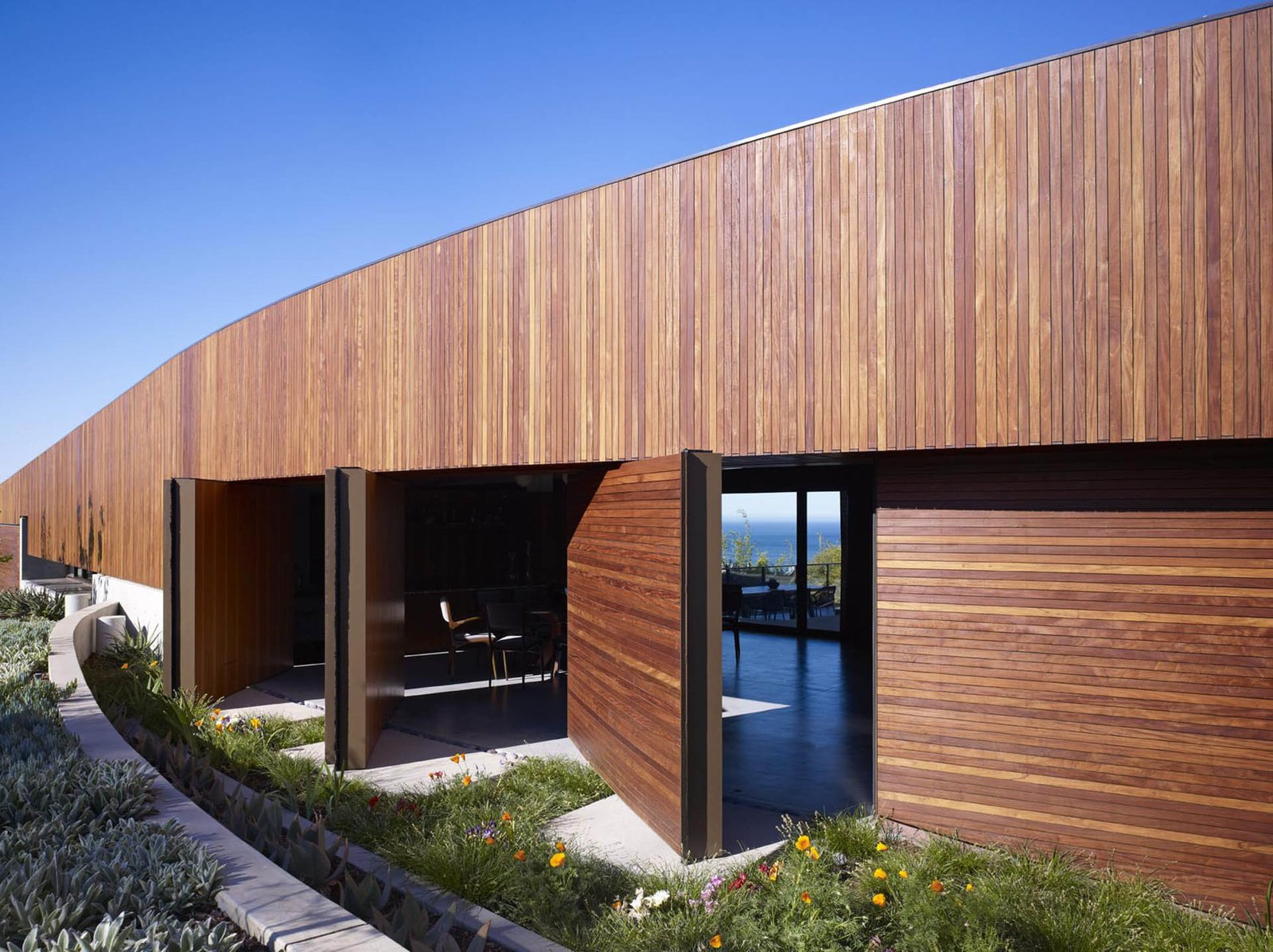 The front door and pivoting wall panels transform this façade when opened, presenting views of the interior, the courtyard and the ocean beyond.  Ziering Residence