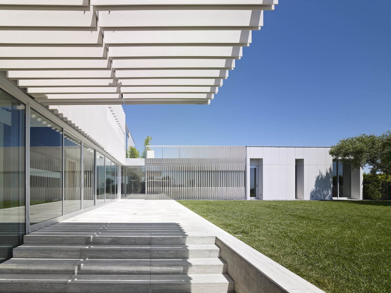 Staring back at the house from its private landscape, a transparent glass main level is topped by the master and family bedrooms.  Oberfeld Residence