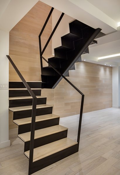 A wood backdrop soars up the back of the stair. The railings kiss the wall and disappear.