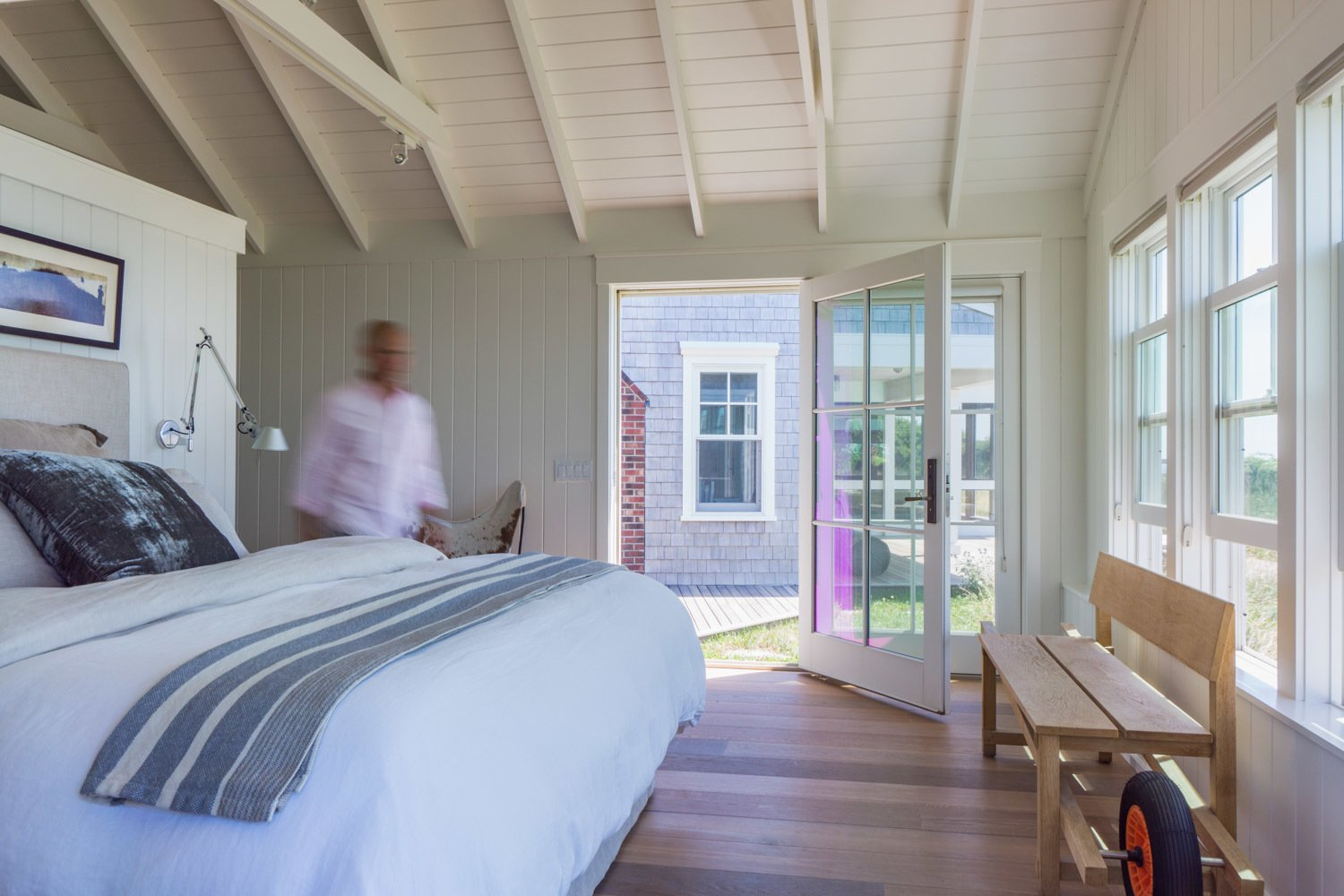 A modest bedroom sits functionally askew to the main part of the cottage to provide a panoramic view of Provincetown harbor - a spectacular view of twinkling nighttime shore lighting as the dunes curve toward the tip of Cape Cod. The open french door leads to a secluded hot tub and deck area.  Corkin House