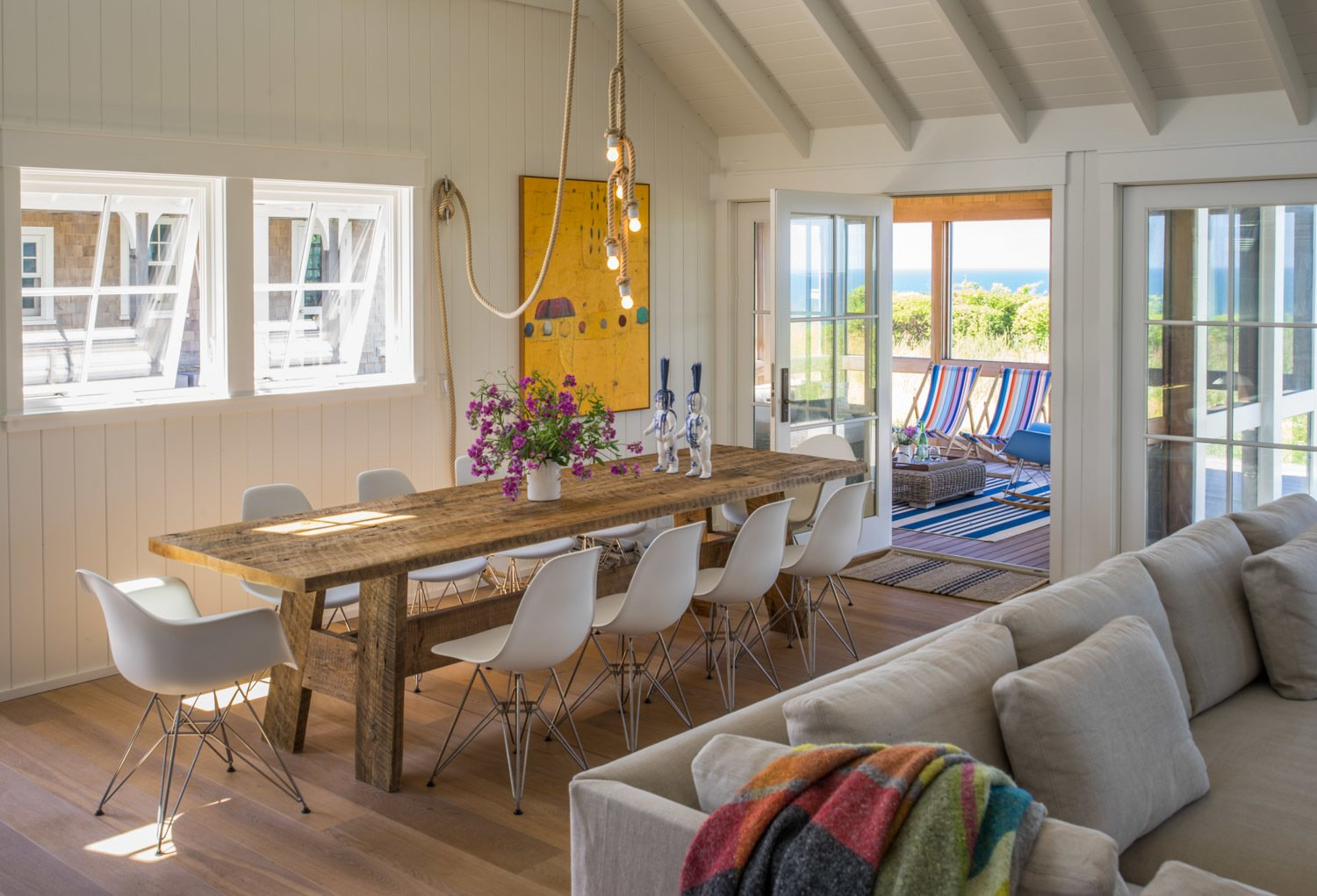 The dining area is furnished with a 10 foot long, rough hewn recycled timber table and contrasting classic Eames chairs.  Corkin House