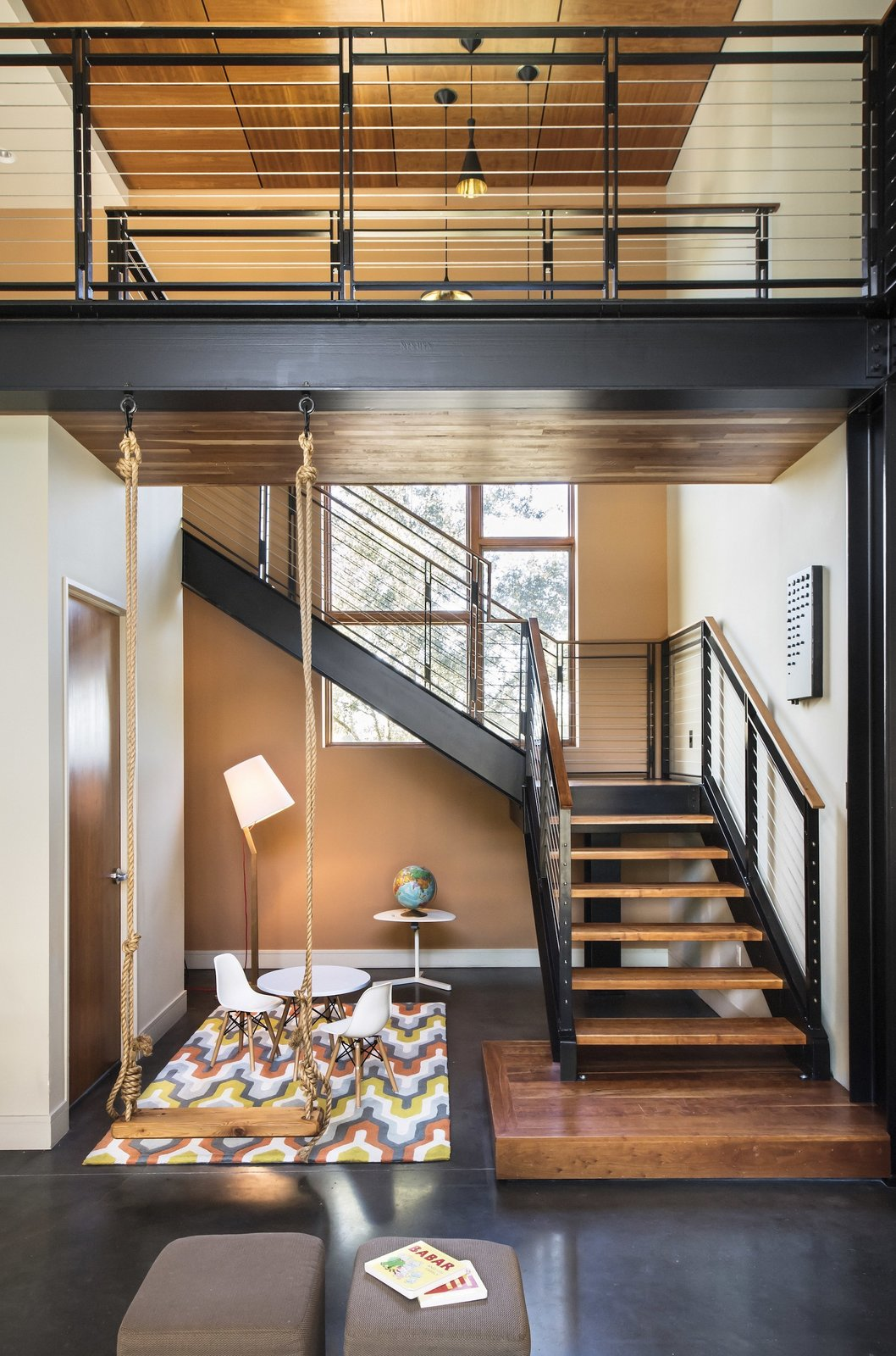 "A wooden swing is anchored into the exposed, steel cross beam that supports the second story. ""It speaks to the playful whimsy of being a grown child,"" says Young, who found the piece at Peg and Awl -- a trove of repurposed treasures -- and thought it would be fun for the space. His kids like it too.   House ideas from 1600 Lakeside"