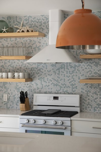 Economical and easy to install, small hexagonal tiles are a classic option for a backsplash. Here, a range of light blues and whites echoes both the off-white cabinetry and countertops and the blues of the nearby beaches in this Florida kitchen.