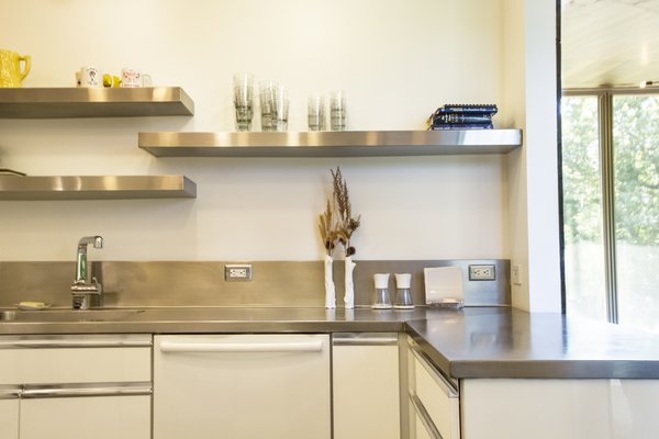 In a modern home in the Illinois River Valley, the kitchen worktop is a seamless, stainless-steel surface with integrated sink and backsplash, custom-fit by Elkay. The sheen on the backsplash helps reflect light in the kitchen, and complements the hardware on the white cabinets.