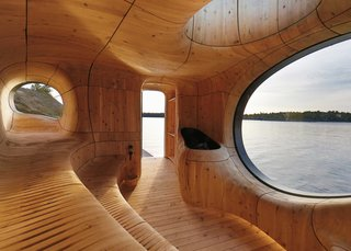 The sinuous interior is lined with CNC-cut wooden panels that define stepped sauna seating and porthole windows.
