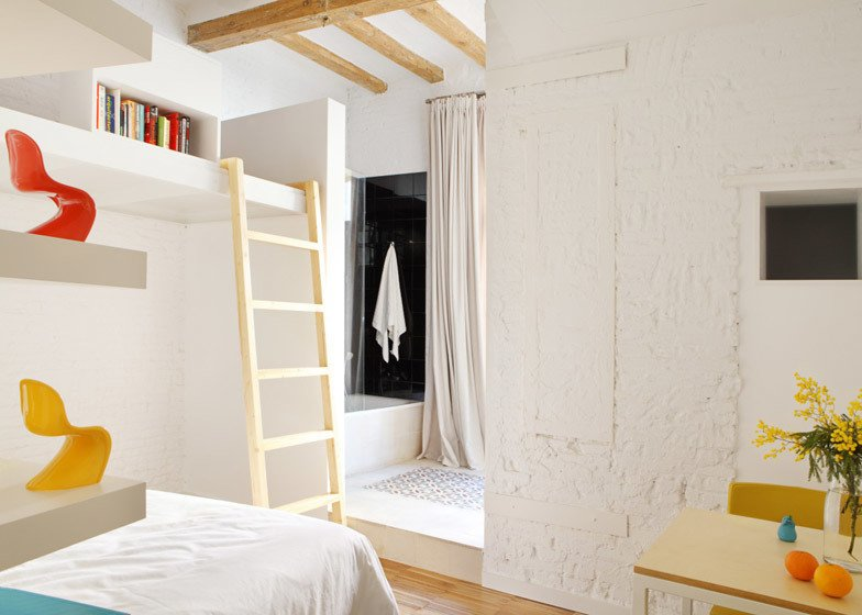 Bedroom with a ladder leading to a loft workspace.