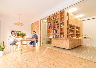 Moveable library-style shelving units slide from side to side to reveal and hide compartments that serve various functions in the Madrid apartment by PKMN Architectures.