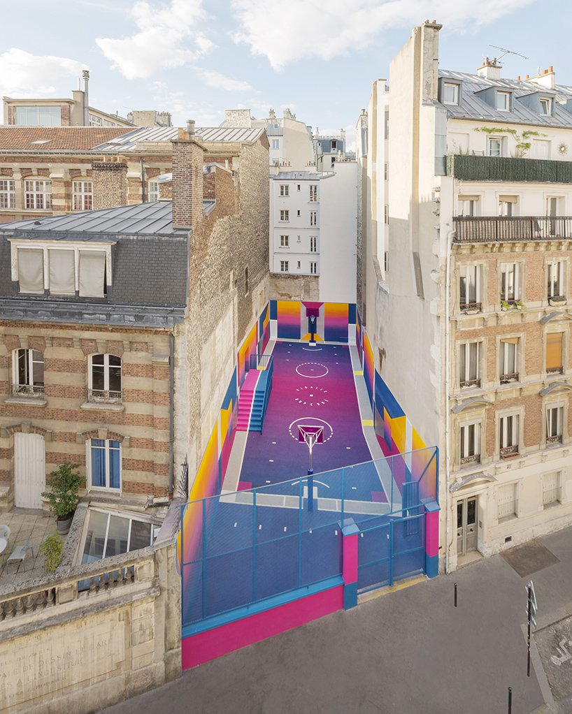 Outdoor, Large Patio, Porch, Deck, and Concrete Patio, Porch, Deck Sandwiched in-between a pair of brick apartment buildings in Paris lies a technicolor basketball court.  Basketball fan and founder of the French fashion brand Pigalle, Stéphane Ashpool collaborated with Parisian creative agency Ill-Studio and Nike to make over the site. The basketball court's walls and floor encircle players in saturated and smooth shades, where shots can be made off of a bright pink backboard. The overall effect is set with a vibrant gradient aesthetic featuring a color palette of high-contrast grape, deep yellows, and bold blues.  Photo 2 of 10 in A Technicolor Basketball Court in Paris