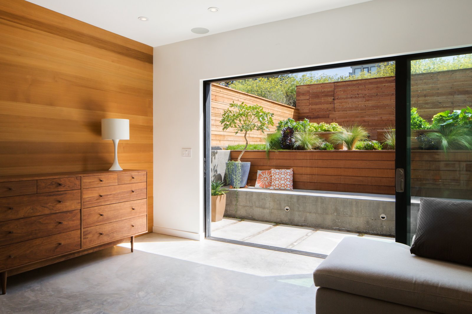 Bedroom, Storage, and Concrete Floor The downstairs family room serves as a guest room for visiting family, the kids' play area and art studio, movie-watching room, and indoor/outdoor living room.  Best Photos from Revamping the San Francisco Vernacular, Modern Design and Technology Serves A Busy Family