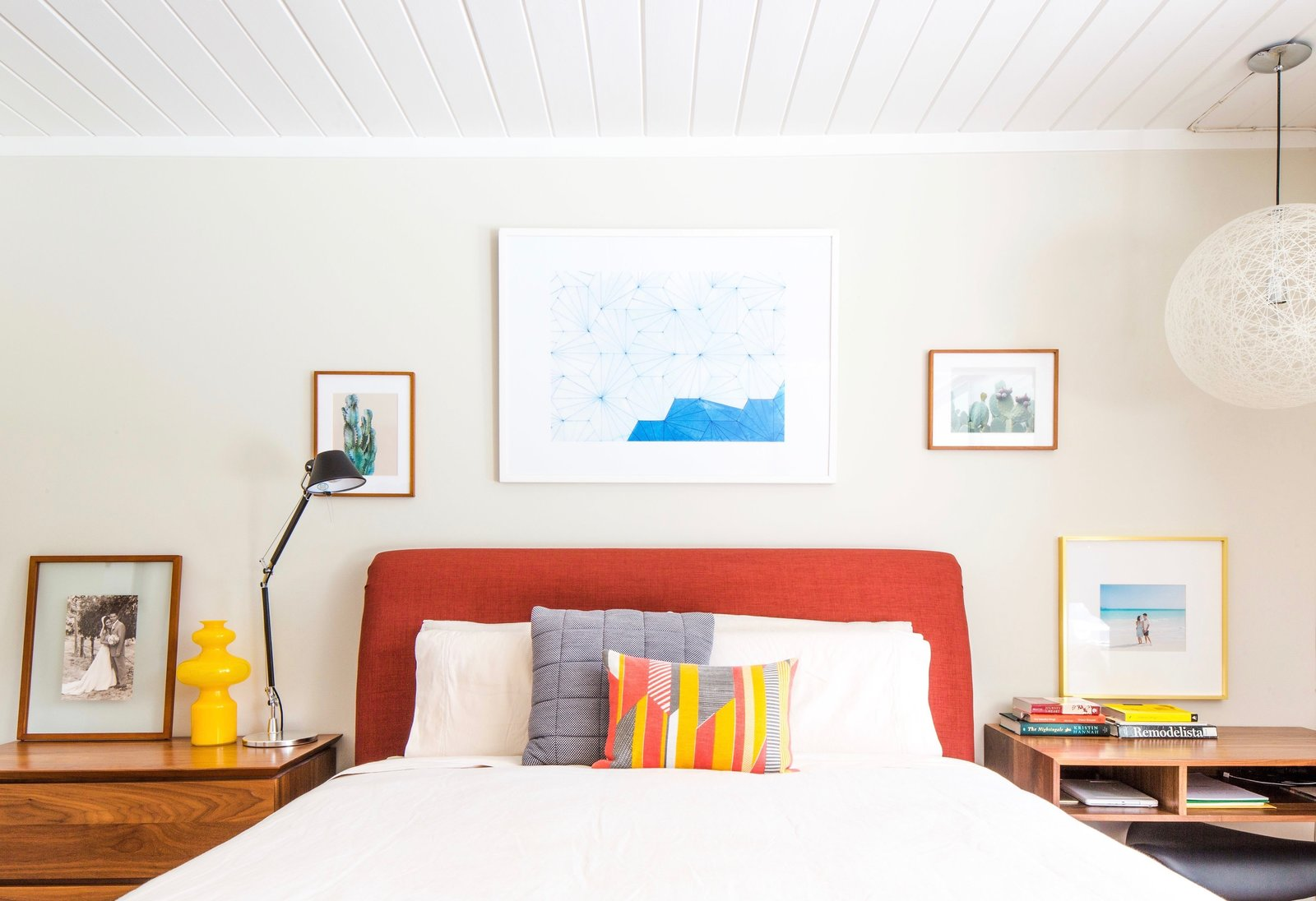 Bedroom, Bed, Night Stands, Pendant Lighting, Table Lighting, and Lamps A few simple pieces of artwork can tie a room together without a huge cost.  Photo 9 of 9 in When to Save Versus Splurge in Your Bedroom Revamp from An Interior Designer Launches Her Career by Renovating Her Family's Midcentury Eichler