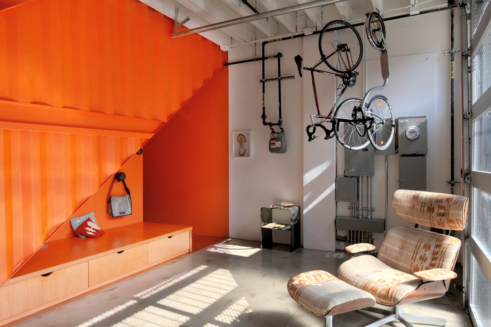 Living Room, Bench, Chair, Storage, and Concrete Floor The architecture is now organized around a polychromatic core volume that extends from the ground floor to the roof terrace.  Photo 7 of 12 in A Brooklyn Carriage House Is Revamped With a Penthouse Made From Shipping Containers