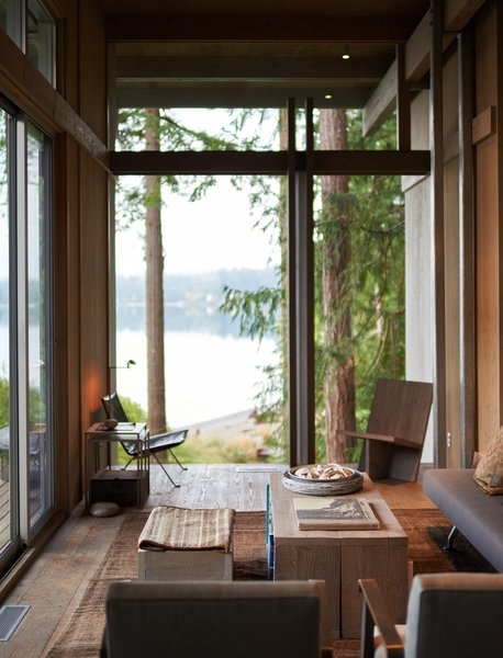 The living room's large wall of glass frames a view of the adjoining grassy field and Puget Sound, visually blending indoors and outdoors.