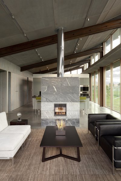 Living Room, Standard Layout Fireplace, Gas Burning Fireplace, Concrete Floor, Sofa, Coffee Tables, Track Lighting, and Chair Glass Farmhouse | Olson Kundig  Glass Farmhouse by Olson Kundig