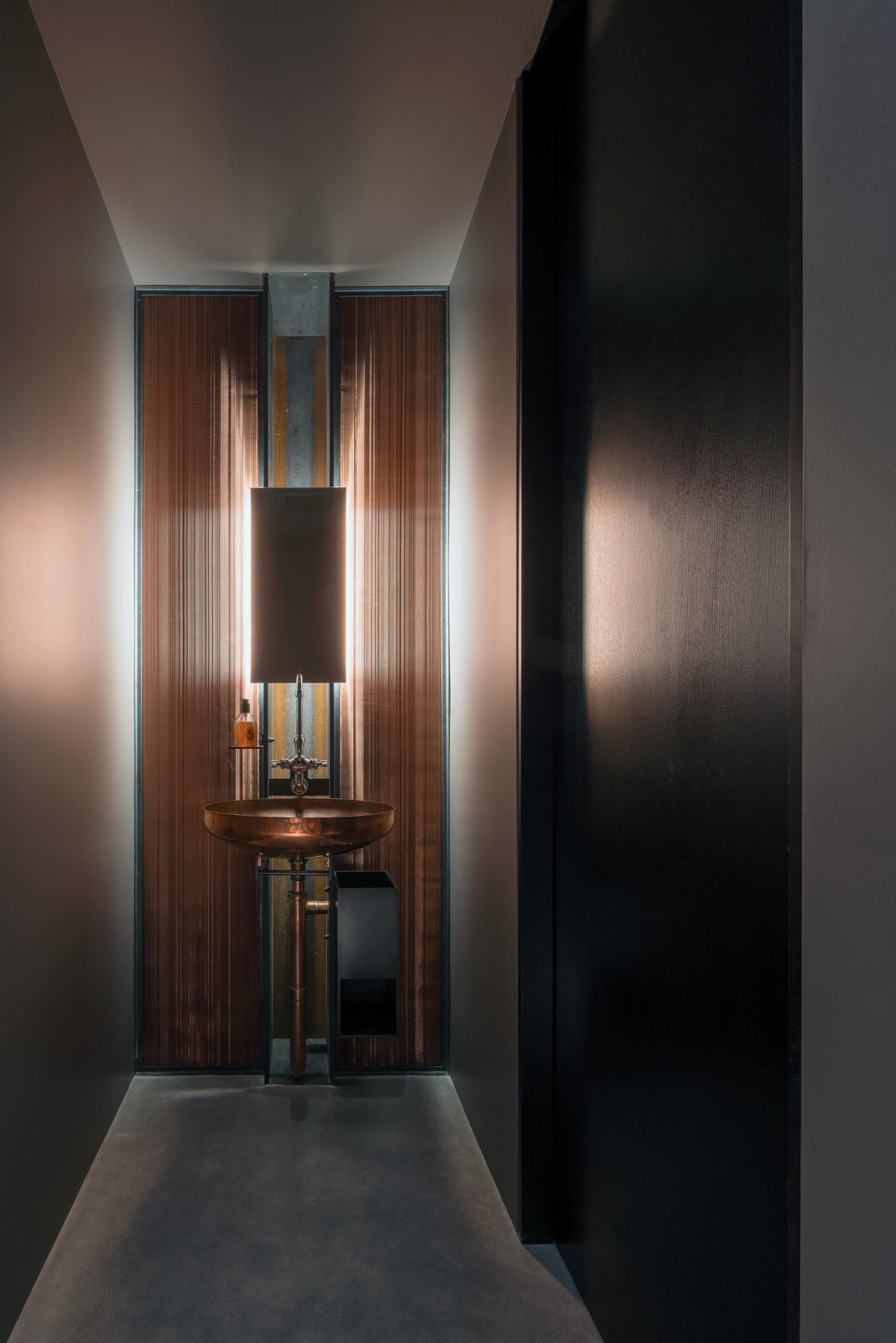 Bath Room, Metal Counter, Concrete Floor, Wall Mount Sink, Recessed Lighting, Wall Lighting, Accent Lighting, and Metal Wall Meg Home | Olson Kundig  Meg Home by Olson Kundig