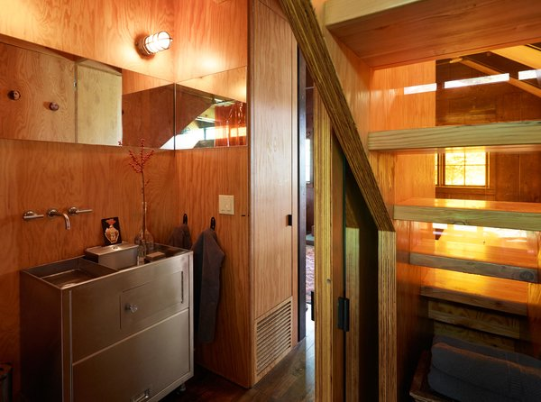 Agate Pass Cabin | In the powder room, a former hospital cart was redesigned into a stainless steel sink and cabinet | Glass relites in the staircase risers act as a window providing natural light and views into the garden.