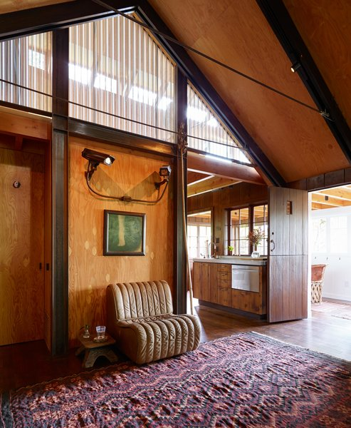 Agate Pass Cabin | A new structural steel moment frame secures all levels of the house to the foundation. The exposed frame screens the bedroom loft. | Artwork: Untitled WJ-1 by Portland artist Leiv Fagereng | : ) is a cast bronze portrait of a security surveillance system by the art collective Sutton/Beres/Culler. For Maskin, the piece references the idea of home surveillance as it relates to neighbors and neighborhoods.