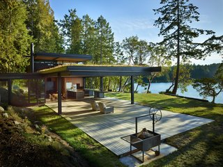 """<span style=""""font-family: Theinhardt, -apple-system, BlinkMacSystemFont, """"Segoe UI"""", Roboto, Oxygen-Sans, Ubuntu, Cantarell, """"Helvetica Neue"""", sans-serif;"""">Olson Kundig's response to tight site logistics was simple: Peel away the walls of the main gathering space to create an expansive indoor/outdoor living area with spectacular views. A hand-cranked wheel connected to a set of gears and chains (like those of a bicycle) allows the nine-foot-tall glass walls—the largest of which is 20 feet long—to move effortlessly. When open, the window walls of Pole Pass Cabin unite the living and kitchen areas with the expansive deck, which is nearly the same size as the building footprint.</span>"""