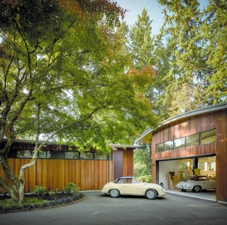 """The adjacent detached garage continues the home's sculptural language with a curving roofline and high windows,"" says architect Olson Kundig. Inside, vaulted ceilings further echo the bright and airy interior of the home's main living space. The garage provides an open workspace that supports the owner's passion for restoring classic cars, as well as weather-protected storage. Just outside, a defined entry and forecourt create a multipurpose, functional space for both parking and play."