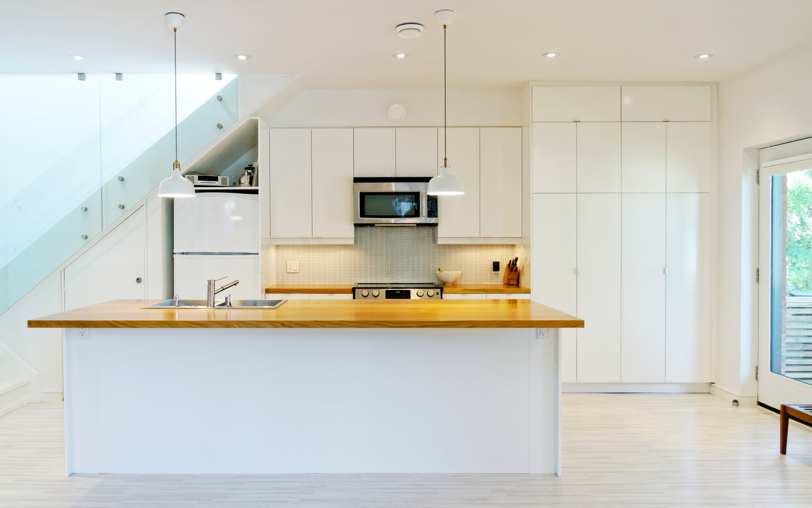 Light Hardwood Floor, Ceiling Lighting, Wood Counter, White Cabinet, Pendant Lighting, Drop In Sink, Microwave, Dishwasher, Staircase, and Glass Railing Our House - Kitchen  Our House by Solares Architecture