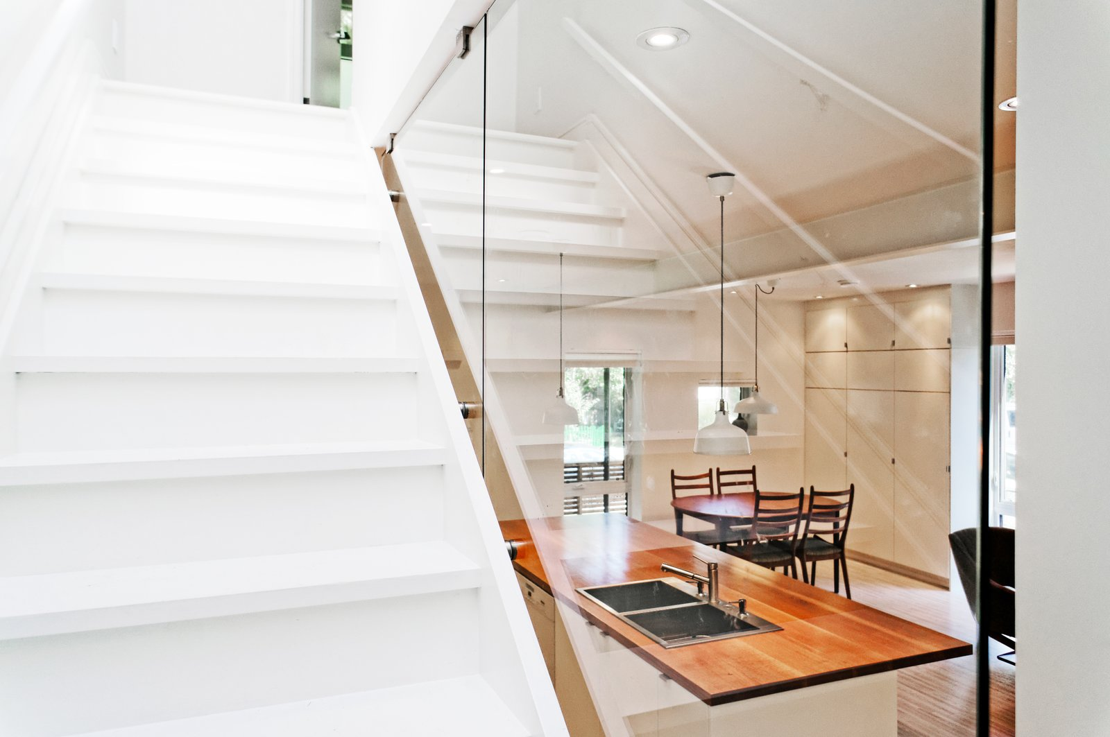 Wood Tread, Glass Railing, Bar, Light Hardwood Floor, Ceiling Lighting, Kitchen, Wood Counter, and White Cabinet Our House - Staircase  Our House by Solares Architecture