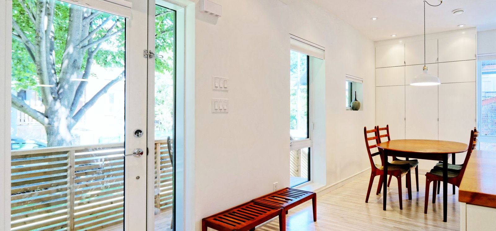 Bench, Ceiling Lighting, Light Hardwood Floor, Dining Room, Table, Chair, and Storage Our House - Front Door  Our House by Solares Architecture