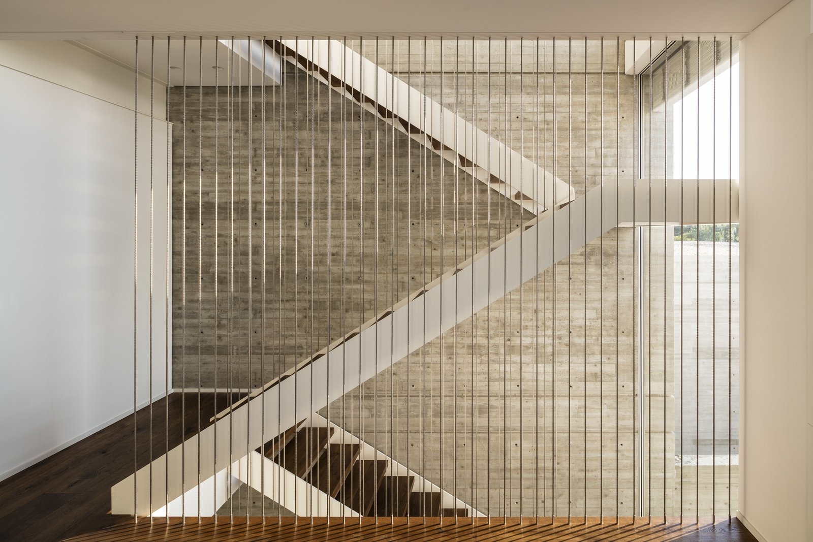 Staircase and Wood Tread At the meeting point of these two masses, public and private spaces, is a vertical axis that cuts the horizontal plane with the use of a staircase that goes through all levels of the house.   Photos from The Dual House