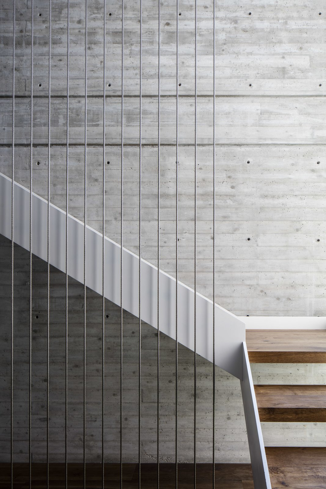 The staircase provides a central, vertical axis between the upper and lower levels.  The Dual House by Axelrod Architects
