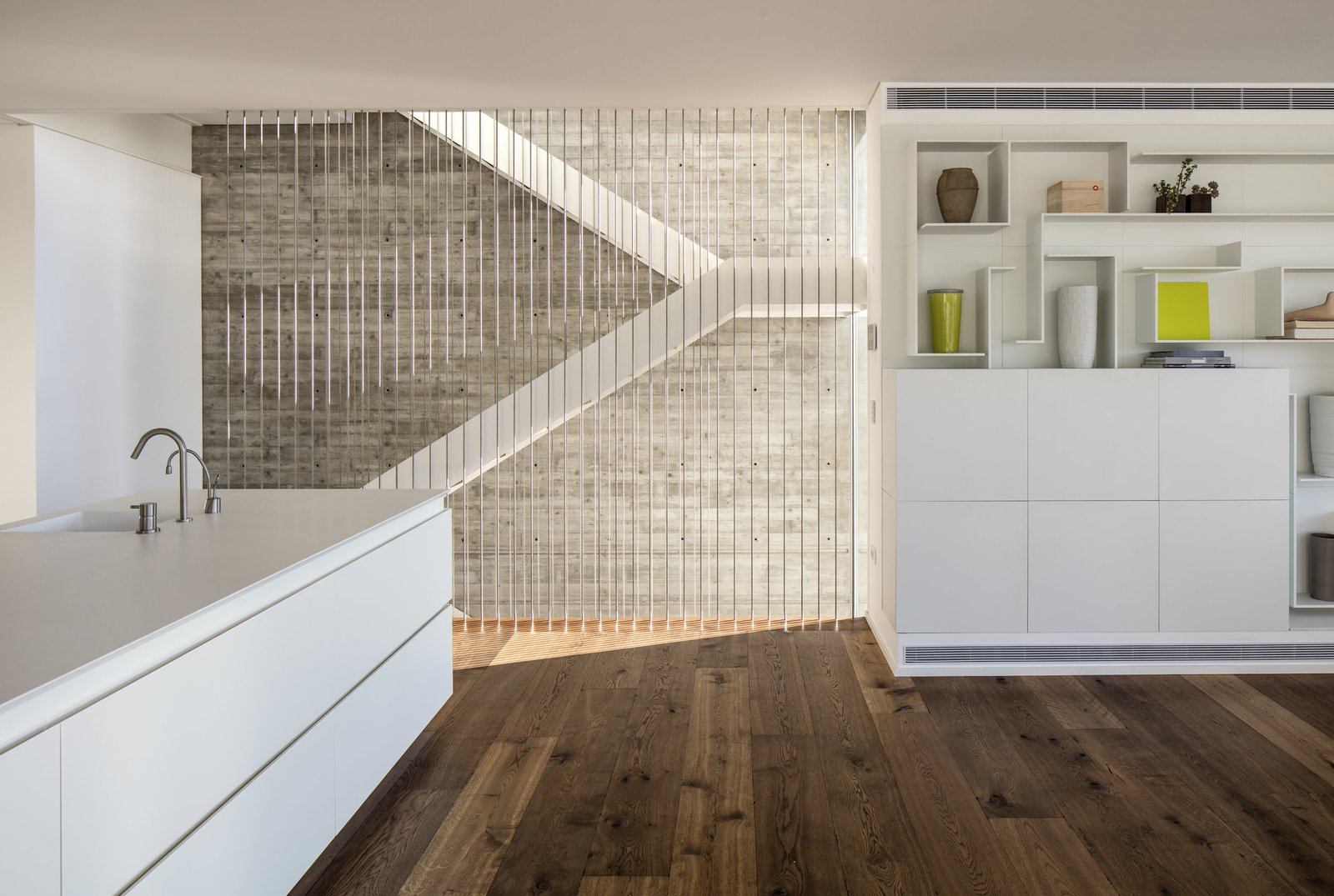 The staircase goes through the center of the house, pictured here adjacent to the open plan kitchen/living area.  The Dual House by Axelrod Architects