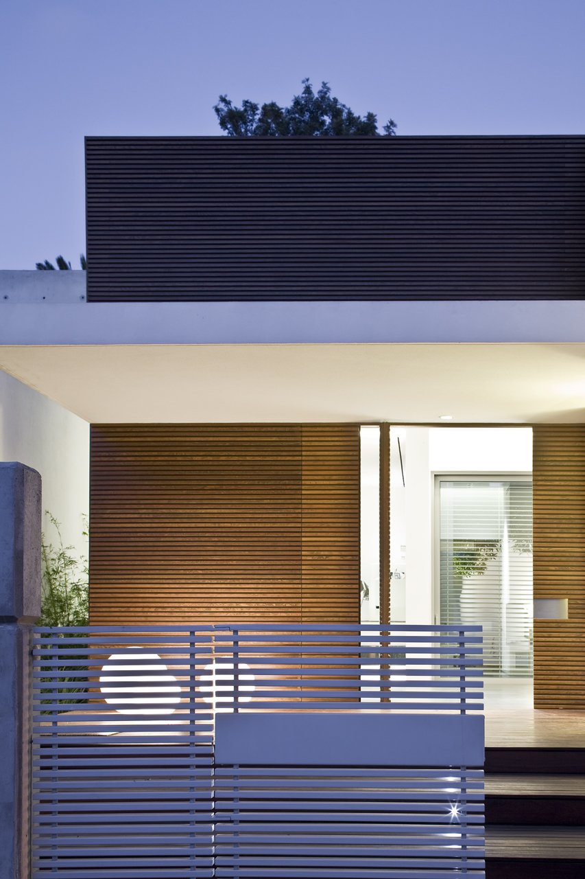 A dramatic front entrance comprised of horizontal wooden slats and a cantilevered canopy.  eHouse by Axelrod Architects