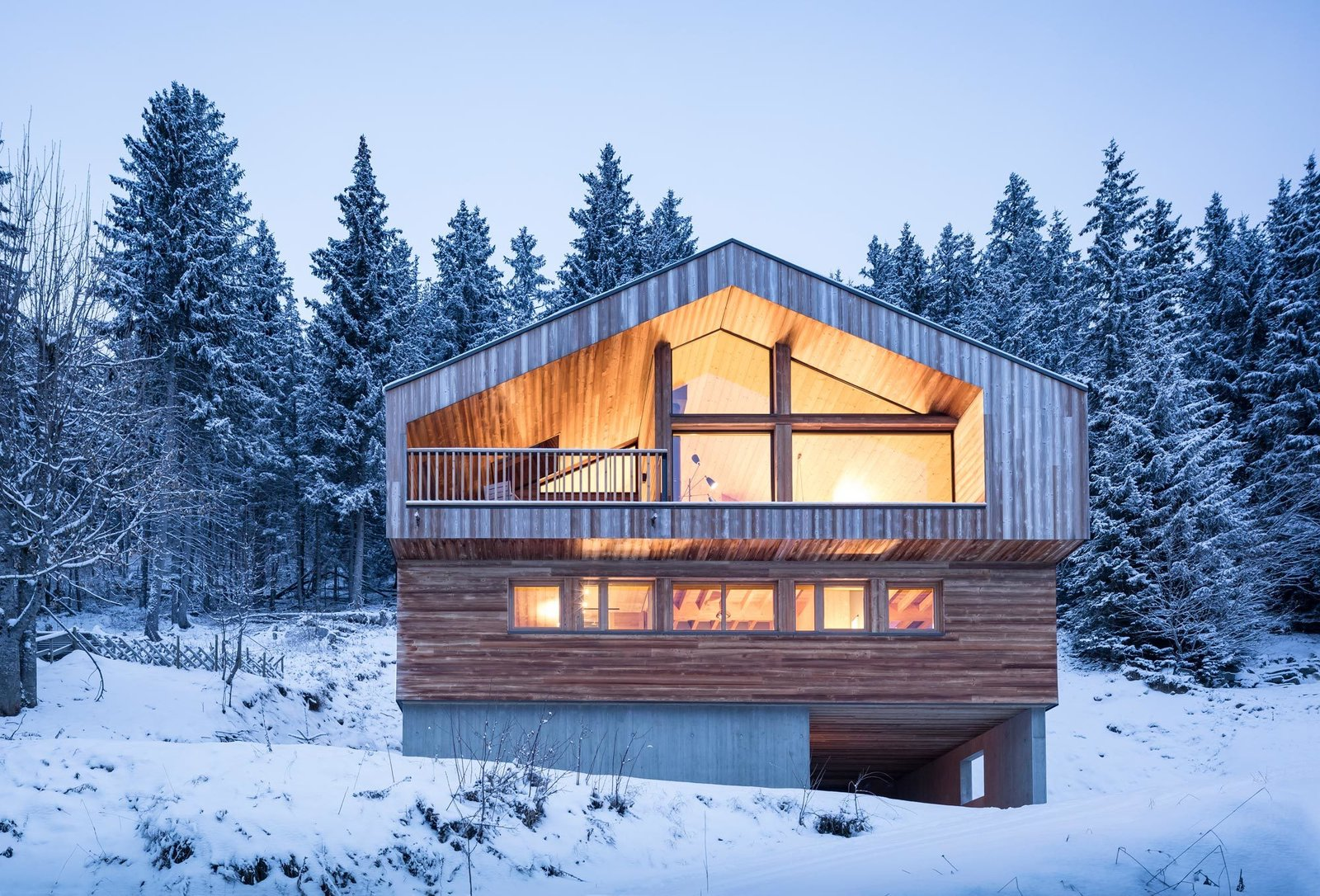 Exterior, Cabin Building Type, House Building Type, Gable RoofLine, Wood Siding Material, and Metal Roof Material The base of this cabin is constructed out of cast-in-place concrete with formwork using the same wood as the floor cladding above.