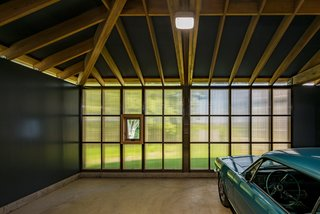 The bronze polycarbonate cladding at the rear of the garage of Cove Site Works carries around at the clerestory level.