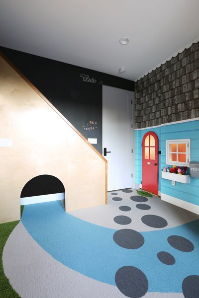 In a home in Los Angeles, a child's bedroom has been outfitted with custom carpeting and millwork, a reading nook under a staircase, a mini door and window, and a magnetic chalkboard wall.