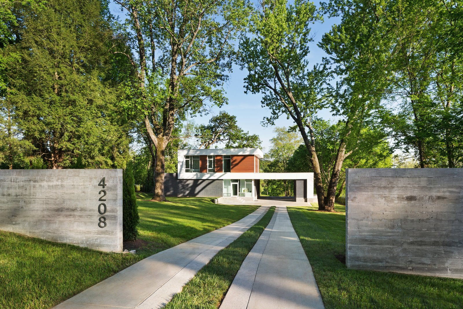 A board formed concrete wall provides a threshold at the arrival and frames a view of the house  Boetger Residence by Chad Boetger