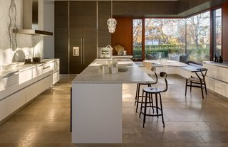 Spacious and highly functional, the polished kitchen features customized bespoke cabinetry. Built-in benches along a glazed corner provide plentiful seating.