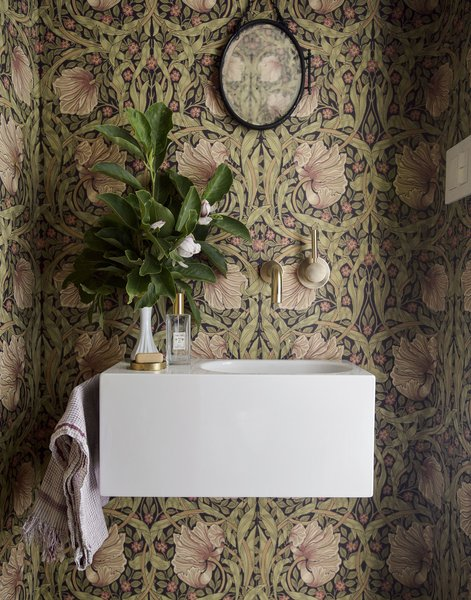 Floral wallpaper adds extra flair to the home's small powder room.