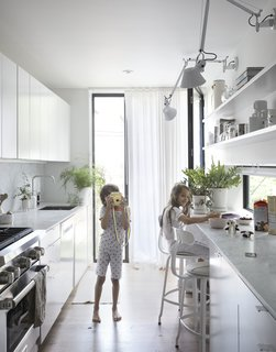 Honed Carrara marble lines the kitchen countertops as well as the backsplash.