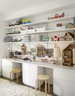 On the second floor, long, open shelves in the kids' bedroom help foster a clutter-free zone.