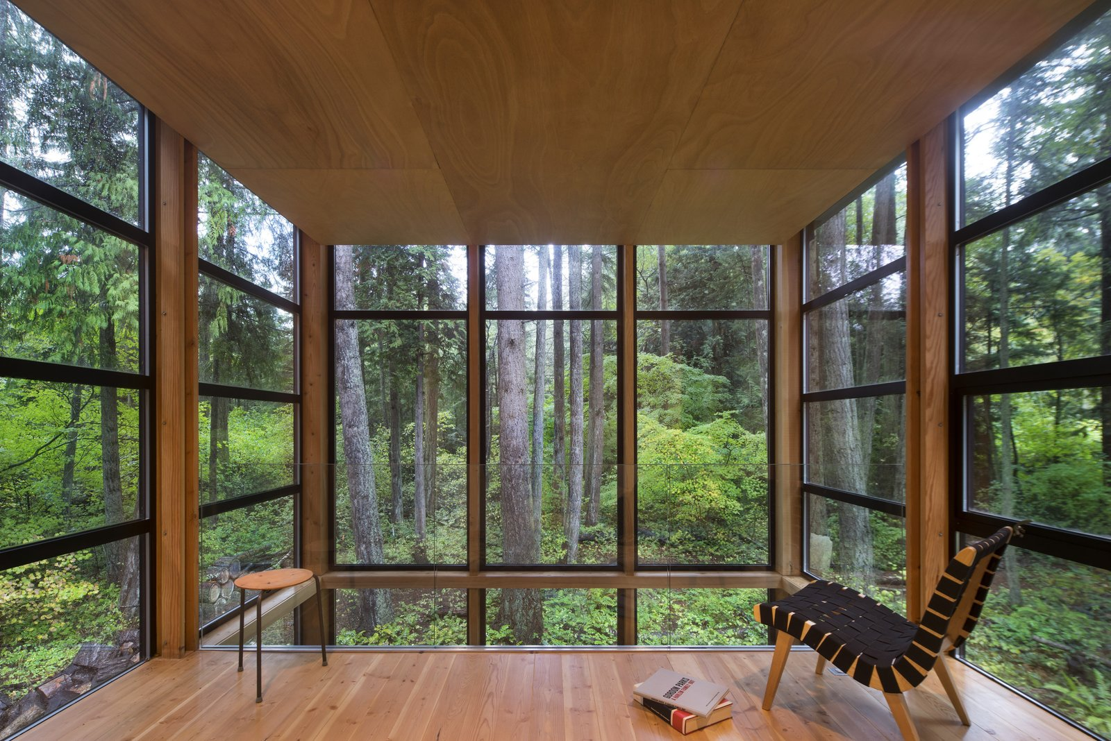 The feeling of being enveloped in the forest is heightened by windows that extend a couple of inches above the slightly dropped hemlock ceiling. This space was originally going to contain the master bedroom until the Owner realized that the view—and the feeling of being in a treehouse—was too magical to waste on a room used for sleeping.  Lightbox by Bohlin Cywinski Jackson
