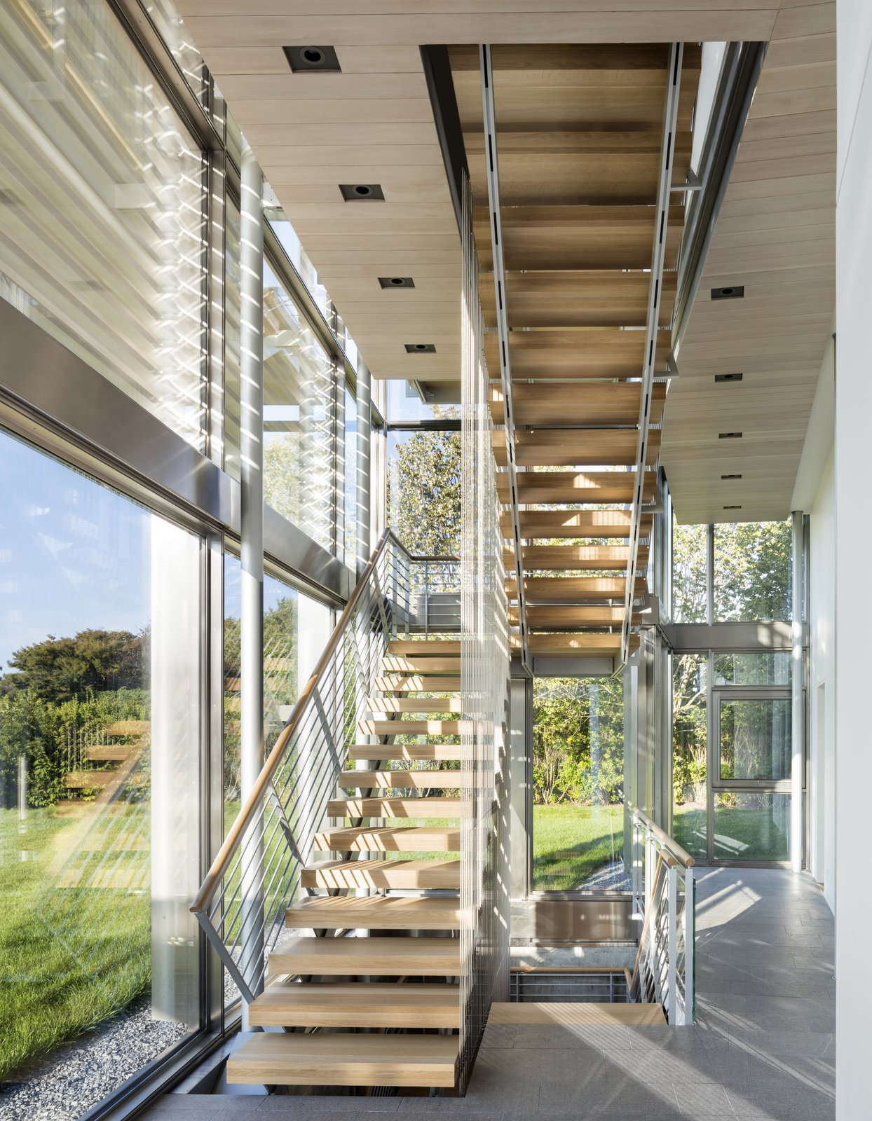 "Staircase, Wood Tread, and Wood Railing Set among fields along the south facing coast of Long Island and within a short walk to the ocean, this Hamptons residence is a quiet refuge for a growing family.    Architect Bohlin Cywinski Jackson says that ""a suspended bridge spans through the double-height space, connecting second story volumes at varying levels and inclining upward and terminating at either end in an open staircase.""  Photo 4 of 6 in Top 5 Homes of the Week With Stellar Staircases from Hamptons Residence"