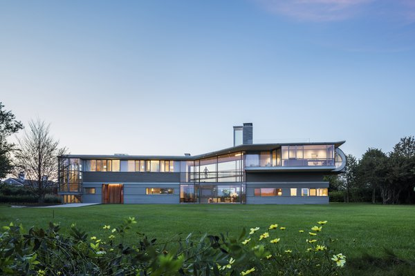 Set among fields along the south facing coast of Long Island and within a short walk to the ocean, this Hamptons residence is a quiet refuge for a growing family and offers extraordinary views of the surrounding landscape. The volume of the house is a two-story wood, steel, and glass structure; transparent walls provide delicacy to the house. Louvered screens and deep overhangs shield the interior spaces from summer sun and allow warm winter light to dip below the roofline.
