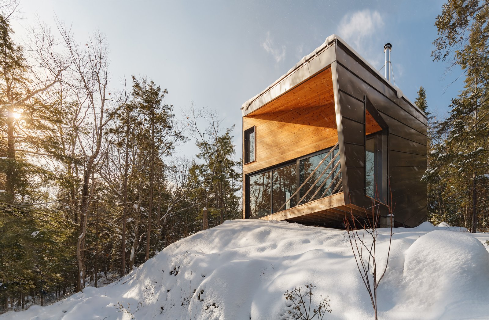 """Exterior, Prefab Building Type, Metal Siding Material, Wood Siding Material, Cabin Building Type, House Building Type, Metal Roof Material, and Shed RoofLine """"The 900-square-foot cabin perches on one piece of granite, projecting precariously over a steep drop-off to afford dramatic eastern views across the valley below,"""" says Isamu Kanda, principal at I-Kanda."""