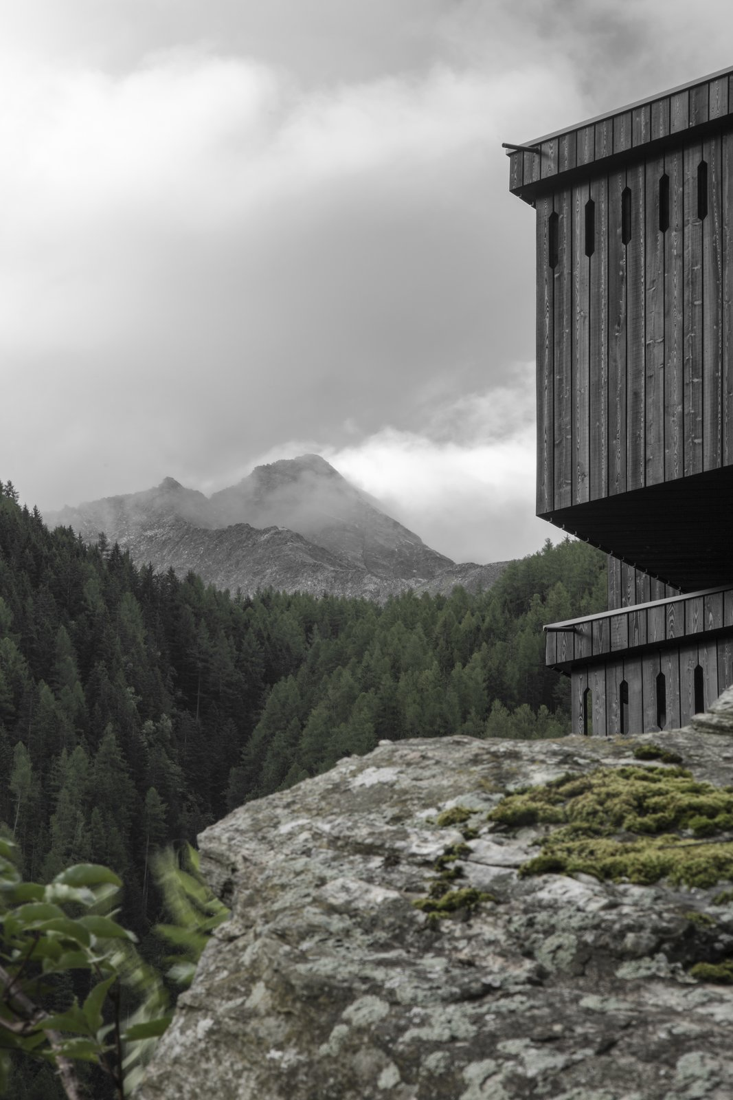 Outdoor, Boulders, and Trees Structurally, the 20-room hotel echoes traditional hiking hotels of the region but offers a modern interpretation—a stripped-down translation  punctuated by an asymmetrical saddle roof and diagonally protruding bay windows that respond to climatic conditions.   Photo 4 of 9 in A Dramatic Hotel in Northern Italy Is a Hiker's Refuge