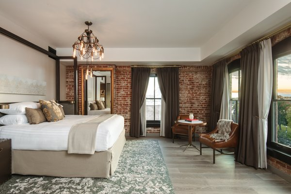 Guests can enjoy plush, comfortable bedding in each room, along with exquisite exposed brick.