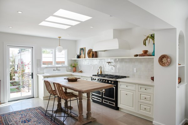 The kitchen's monochromatic Italian farmhouse aesthetic was achieved by inspired design choices, such as a high back farmhouse sink, zellige tile backsplash, La Cornue range, built-in range hood, limewash paint, and imported limestone flooring.