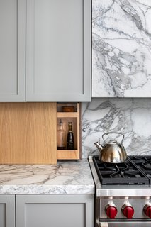 Stucker and Veal custom designed and built the kitchen cabinets, finishing them in Farrow & Ball paint (Lamp Room Grey) to compliment the stone and wood.