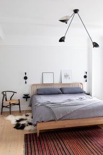 Light hardwood, custom lighting, and bright textiles give new life to the once-drab master bedroom.