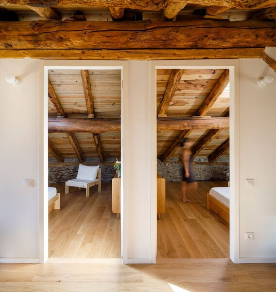 The bedrooms feature stone walls and rustic timber ceilings that slope toward the floor.