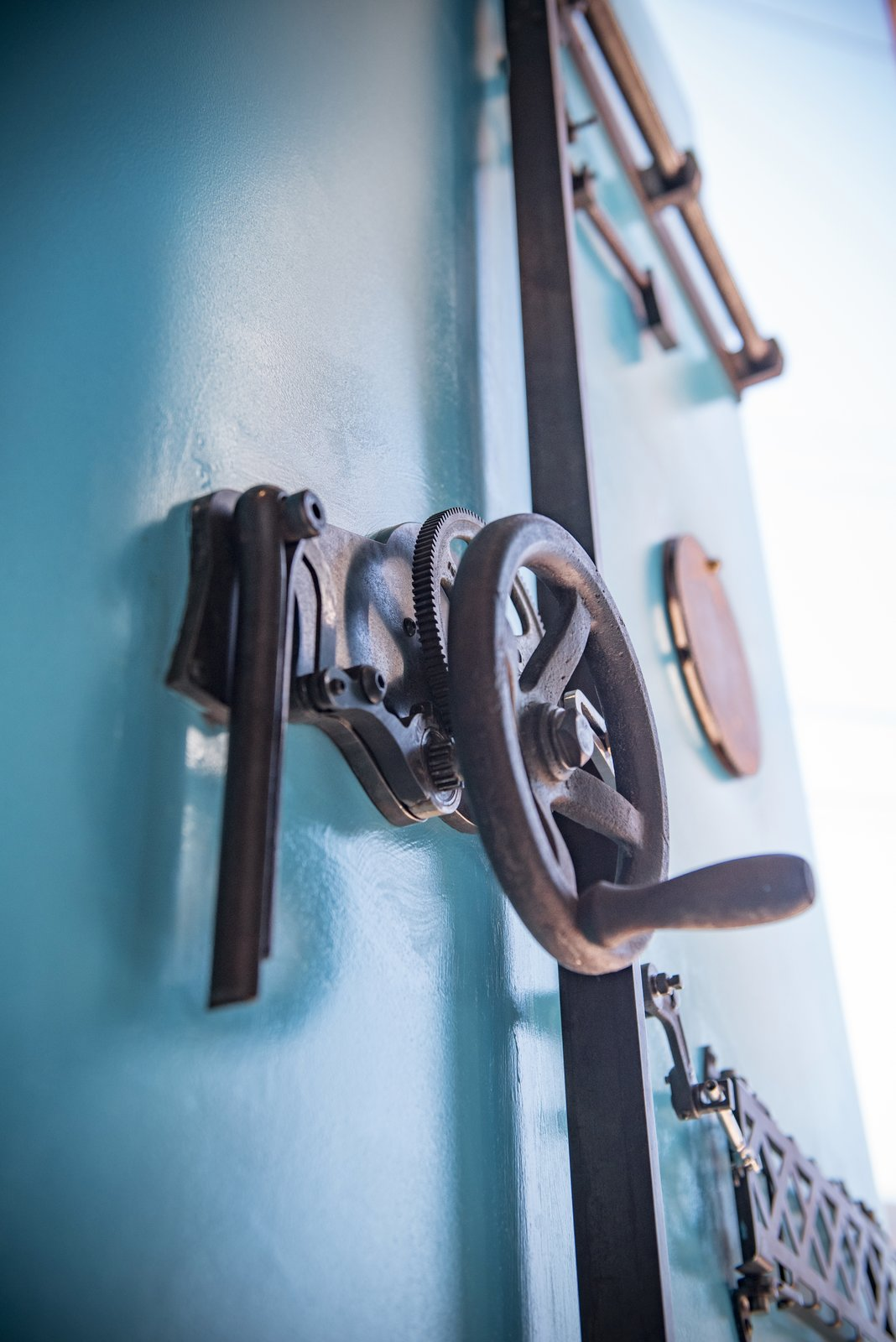 Rear view of custom pivot door made from up-cycled clock parts and repurposed  metal components that function to lock up.  Designed and crafted by the FunktionArt Design Compound.  Studio GoodLight by Liesa Cole