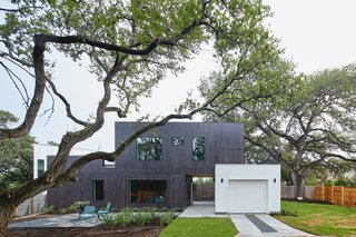 In Austin, Texas, this 1,100-square-foot accessory dwelling unit, called The Chelsea, splits a lot with the main house. The ADU responds to the lot by dodging the heritage trees to the north while creating a very spacious front yard. There is a garage that blocks a dogtrot and the living area of the house from the setting sun; the larger windows are concentrated on the northern side of the lot for plenty of natural lighting while reducing the heat gain in the summer and encouraging passive cross-ventilation.